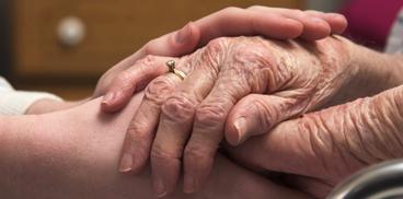 immagine di due mani che si stringono a causa del decesso del partente o amico caro